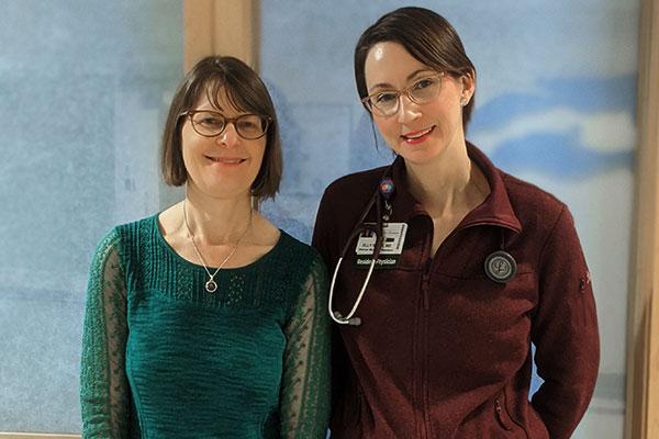 Dr. Halle Sobel and Dr. Elly Riser pose in a hallway of the UVM Medical Center